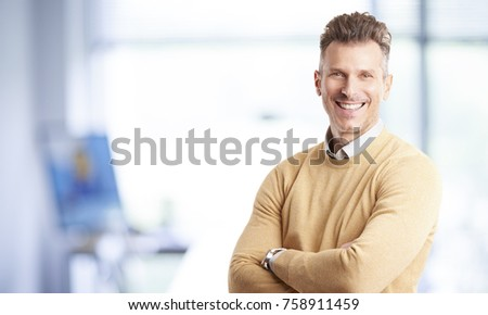 A casual marketing director businessman standing with arms crossed in the office.  #758911459