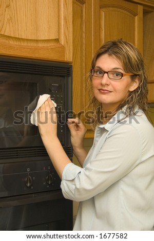 A casual women using a disinfectant wipe to clean the kitchen microwave oven.