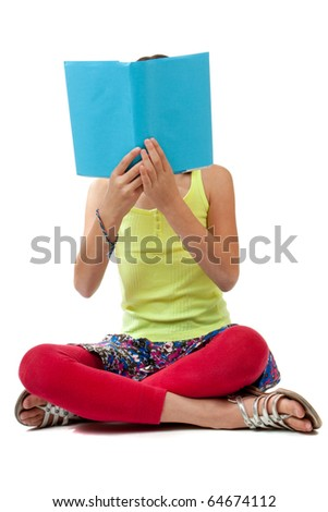 A casually dressed school age girl sits crossed legged and holds up a book with a blank blue cover up over her face.