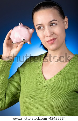 A casually dressed young woman rattling her savings in a piggy bank.