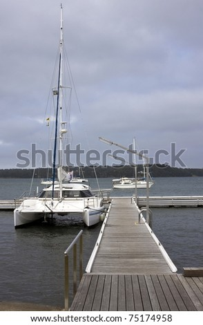 A catamaran moored in a jetty and the wooden path leading to it against the backdrop of a overcast sky