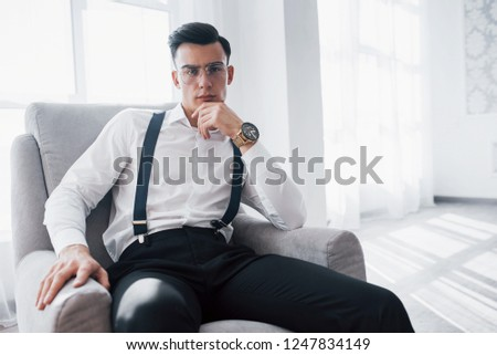 A catchy look. Close up photo of attractive guy in the glasses and stylish wear sitting on the chair.