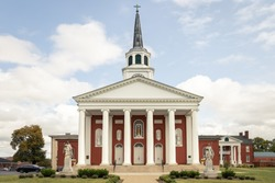 A Catholic Church in Bardstown, Kentucky is made out of red brick with a tall white steeple and pillars