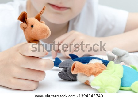 A caucasian boy playing different roles by using finger puppets, toys for expressing his emotions, agression, fear and freandship as a part of psychotherapy. #1394343740