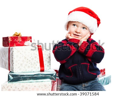 A caucasian boy wearing a santa hat with a lot of christmas gift