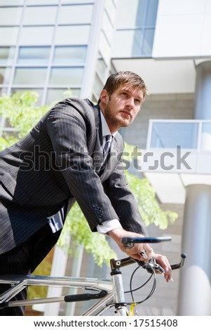 A caucasian businessman riding a bike to work, can be used for green or gas savings concept