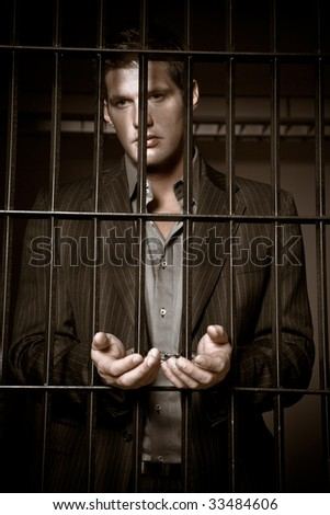 A caucasian businessman sitting in jail handcuffed
