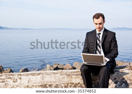 A caucasian businessman working on his laptop outdoor