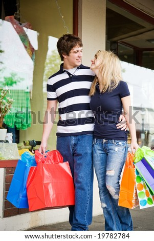 A caucasian couple carrying shopping bags walking in an outdoor mall