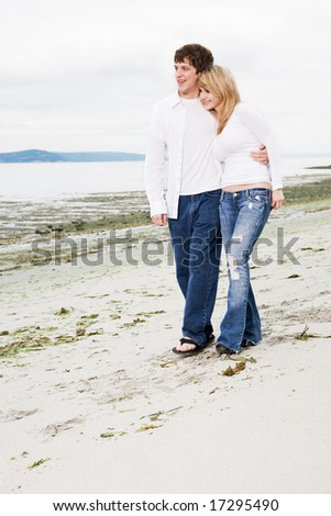 A caucasian couple in love walking on the beach