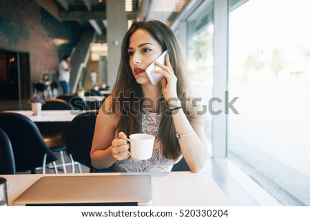 A caucasian female freelancer is talking on a phone while sitting in a cafe with a portable computer on a table. Young attractive business woman is making a business call during the lunch break.