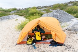 A Caucasian female traveler inside the camping tent in Coral beach strand, Galway, Ireland