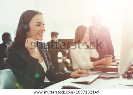 A caucasian-looking woman looks into the camera at the office. She works in the call center. She smiles. Working hard woman concept.