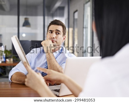 a caucasian male interviewer looking skeptical while listening to an asian female interviewee.
