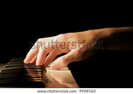 A caucasian male's hand playing a keyboard