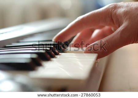 A Caucasian male's hand playing a piano in dramatic lighting