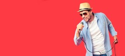 A Caucasian man in a hat and sunglasses sings a song into the microphone. Vocal performance of the song. Advertising banner for karaoke club or bar. Emotional singer. Studio portrait on a red
