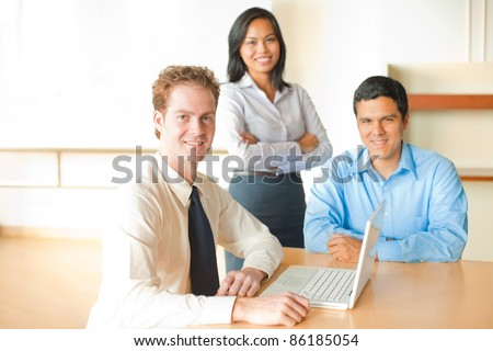 A caucasian man leads a business meeting with an Asian female and latino male