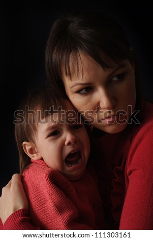 A Caucasian mother with a sad crying daughter on a dark background - stock photo