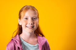 A Caucasian teenager girl with red hair and freckles posing for a portrait over yellow background with copy space. Concept of confident and assertive young females. Gender equality and women's rights.