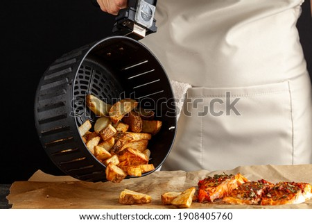 A caucasian woman chef is dumping fresh made fried potato chunks on a piece of baking paper which has three oven roasted marinated salmon fillet with basil and pepper on top. Homemade fish and chips.