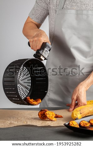 A caucasian woman is pouring freshly made plantain chips (Platanos Maduros) onto baking paper for cooling. She holds the handle of air fryer basket. Air fryer makes it low calorie compared to regular. Foto stock ©