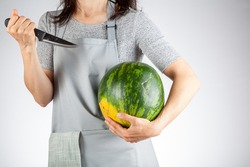 A caucasian woman is preparing to stab a watermelon using a sharp kitchen knife. A versatile image for summer fruits as well as a demonstration of force, metaphorical passive aggressive behavior