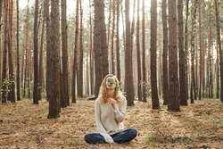 A Caucasian woman outdoors covering her face with a fir twig. The concept of unity with nature and wellness