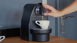 A caucasian woman's hand is pushing a button on the capsule coffee machine to extract espresso in a white ceramic cup. Grey wall in the background. High-resolution jpg photo