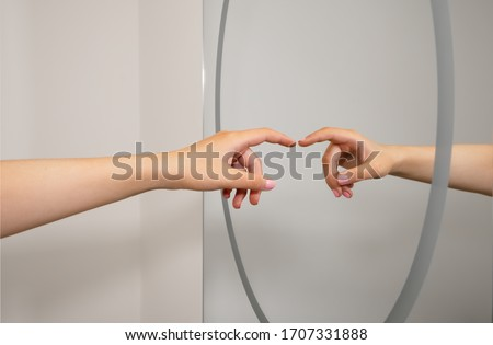 A caucasian woman's hand reflected in a clean bathroom mirror as she reaches out and almost touches. A representation a social distancing and hygiene concept.  Сток-фото ©
