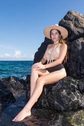 A caucasian woman with sun hat sits in the sun on a coastal rock looking at the camera. Rocky Beach Background