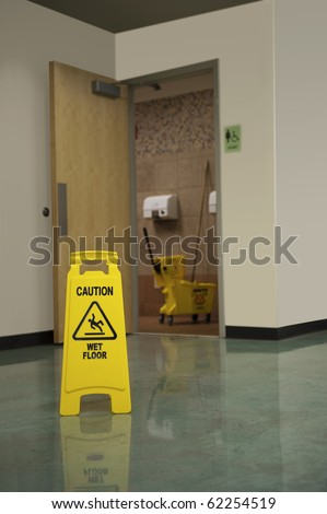 A Caution Sign warns people of a wet floor in front of the women's restroom