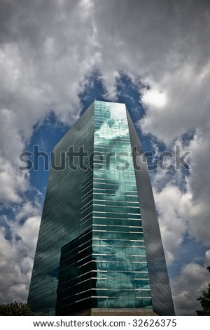 A CBD business building reflects the stormy sky that threatens above it. - stock photo