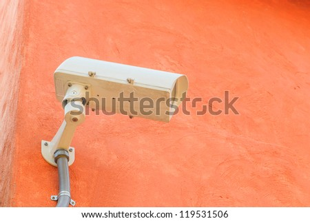 A CCTV camera on a wall at the entrance door.