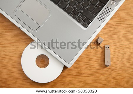 A CD and USB Memory stick with a laptop on a desk