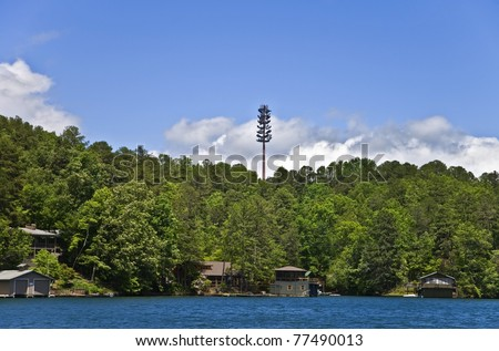 A cell tower high above the tree line over homes and a lake.