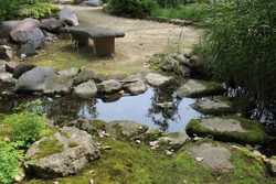 A cement bench at the end of a trail leading to a small pond and streambed surrounds by moss covered rocks at the Rotary Botanic Gardens in Janesville, Wisconsin, USA