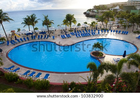 A centered, birds eye view shot of an empty beach resort swimming pool.