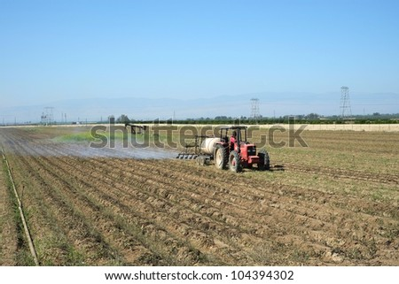 A Central California farmer applies heat from propane burners to plants in potato field to improve the harvested quality