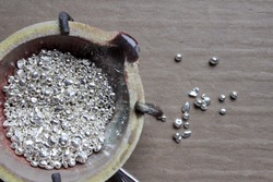 A ceramic crucible or melting pot with grains of sterling silver 925 for jewelry making after hand smelting in workshop. One of the two major precious metals on the market. Separate granules on table.