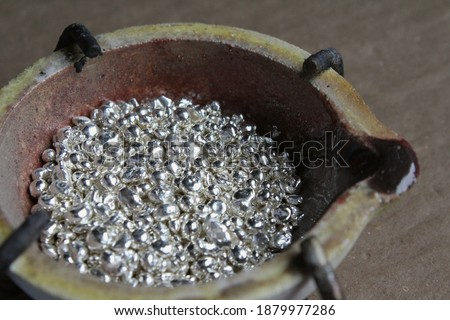 A ceramic crucible or melting pot with grains of sterling silver 925 for jewelry making after hand smelting in a workshop. One of the two major precious metals on the market. Stock photo ©