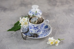 A ceramic cup of green tea with jasmine and a beautiful clock on a chain inside.