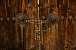 a chain locked wooden door, brown antique door