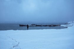 A chain of footprints in the newly fallen snow. Snowfall in the evening twilight. A lonely figure of a man looks at the blue water of Lake Baikal and the port of abandoned ships.