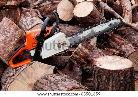 A chain saw sitting on a pile of logs