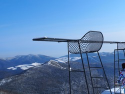 A chair surrounded by the snow mountains in winter