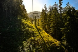 A chairlift leading to the Kaiser Mountains near Kufstein, Austria in the golden evening sun.