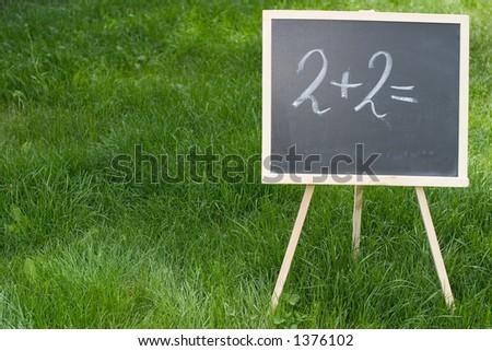 "A chalkboard standing in the grass and with ""2+2="" written on it."