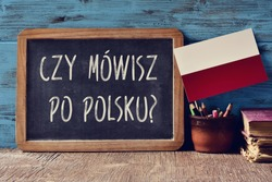 a chalkboard with the question czy mowisz po polsku?, do you speak Polish? written in Polish, a pot with pencils, some books and the flag of Poland