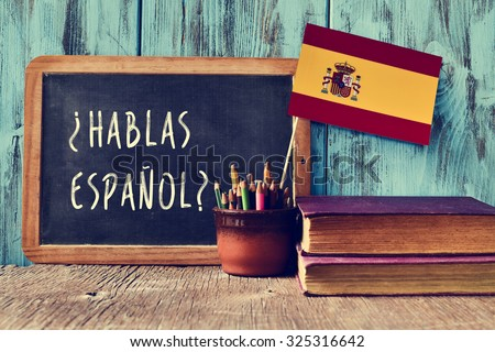 a chalkboard with the question hablas espanol? do you speak Spanish? written in Spanish, a pot with pencils and the flag of Spain, on a wooden desk